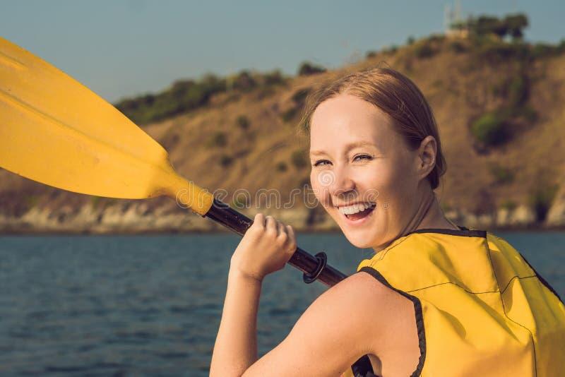 Mujer joven sonriente kayaking en el mar Mujer joven feliz canoeing en el mar en un día de verano fotografía de archivo libre de regalías