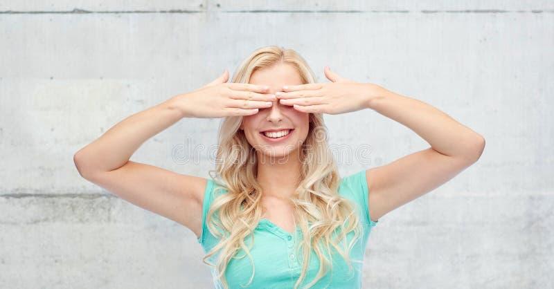 Mujer joven sonriente o muchacha adolescente que la cubre ojos fotografía de archivo