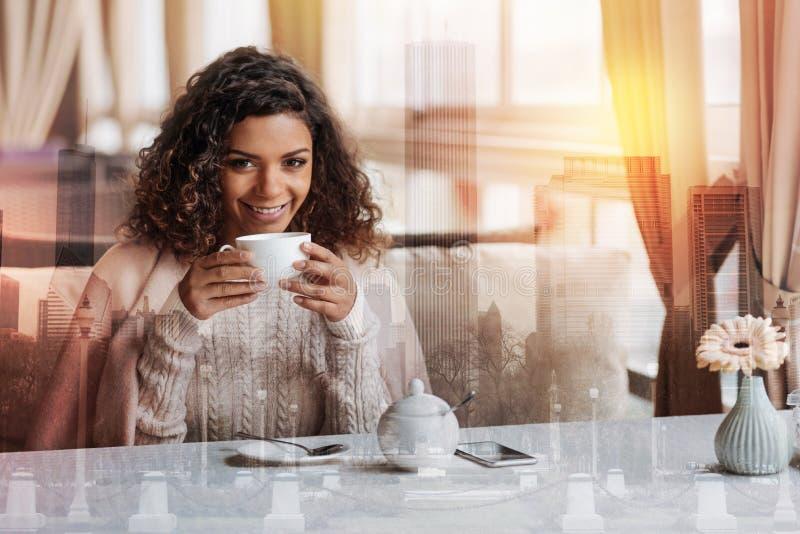 Mujer joven sonriente preciosa que se sienta en la tabla y el té de consumición imagenes de archivo