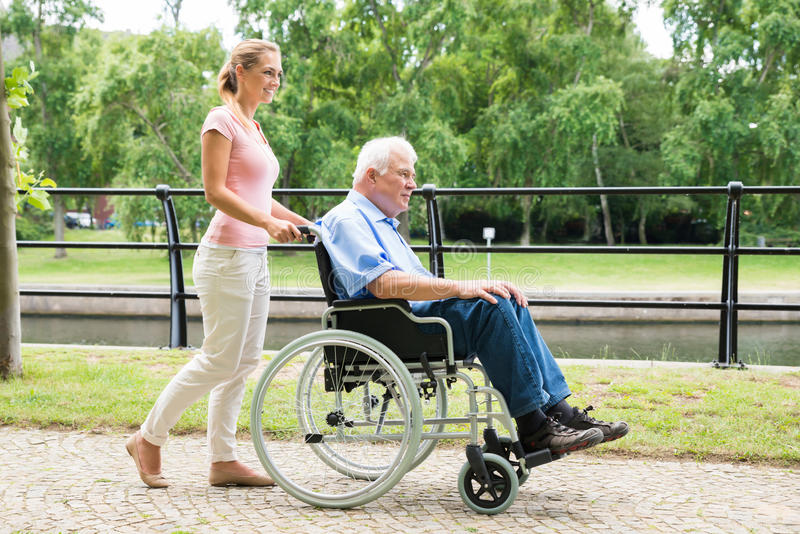 Mujer joven sonriente que ayuda a su padre discapacitado On Wheelchair fotos de archivo