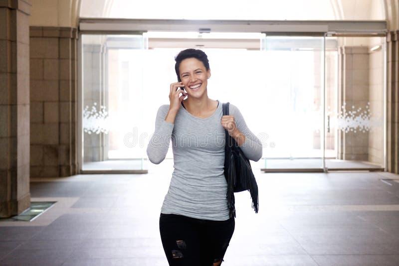 Mujer joven sonriente que camina con el teléfono celular y el bolso imagen de archivo libre de regalías