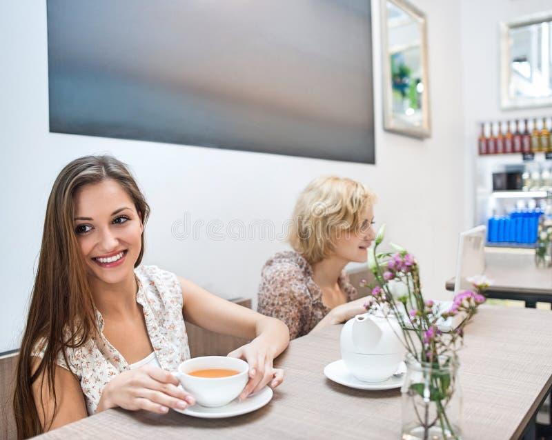 Mujer joven sonriente que come café en café foto de archivo