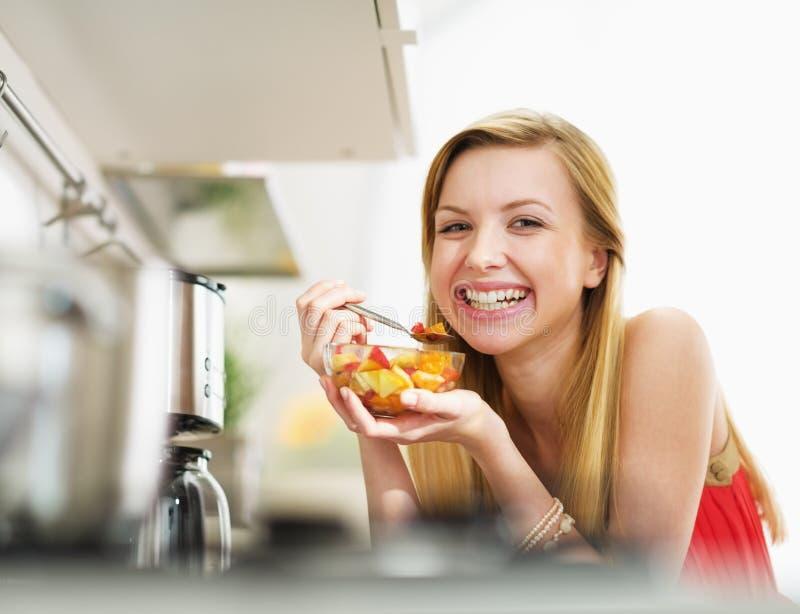 Mujer joven sonriente que come la ensalada de frutas frescas en cocina imagen de archivo