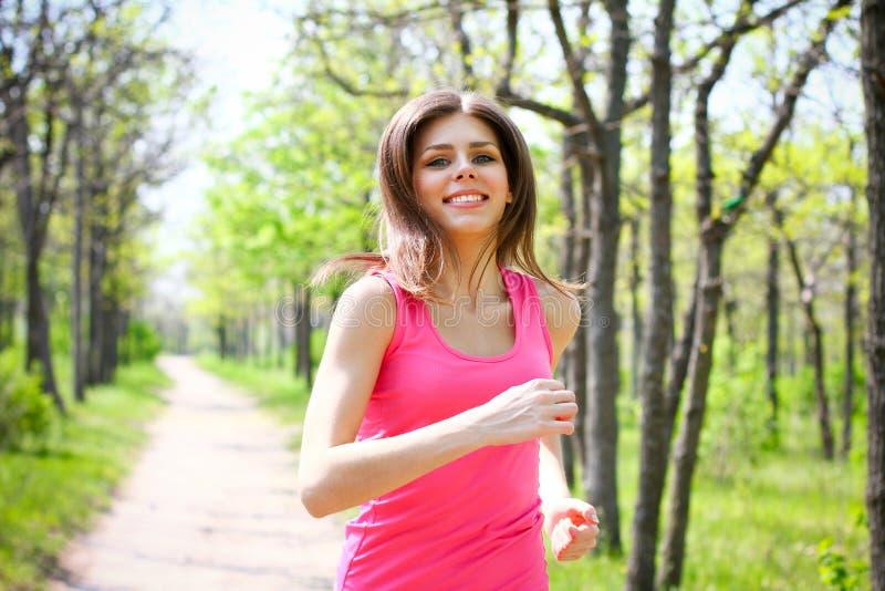 Mujer joven sonriente que corre en parque del verano imagen de archivo