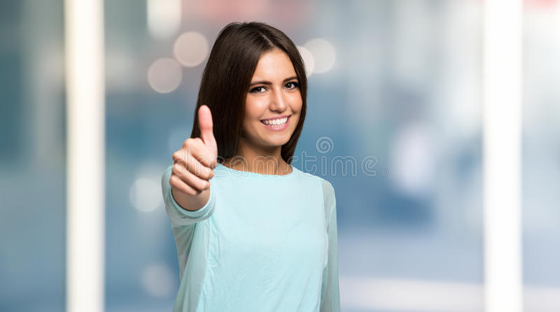 Mujer joven sonriente que da los pulgares para arriba fotos de archivo