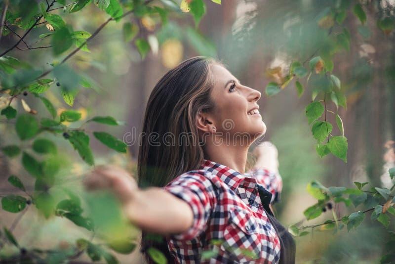 Mujer joven sonriente que disfruta del aire fresco y de la naturaleza fotografía de archivo