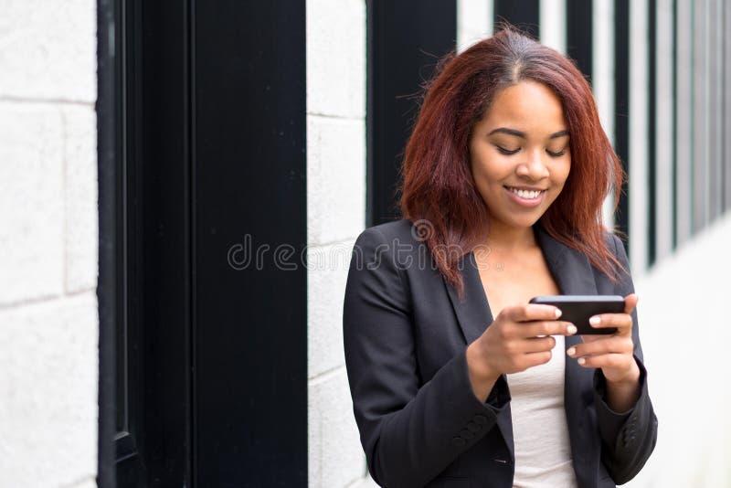 Mujer joven sonriente que envía un mensaje de texto fotos de archivo libres de regalías
