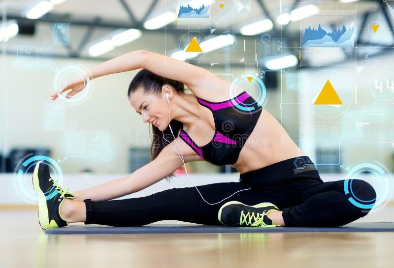 Mujer joven sonriente que estira en la estera en gimnasio imagen de archivo libre de regalías