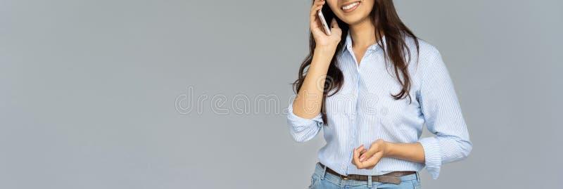Mujer joven sonriente que habla en el teléfono aislado en el fondo, bandera imagen de archivo libre de regalías
