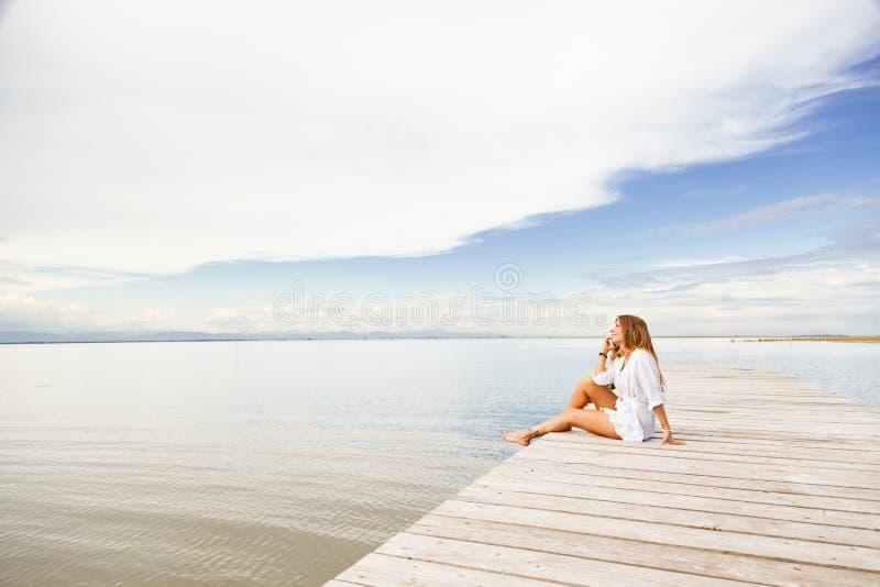 Mujer joven sonriente que habla en el teléfono en un embarcadero foto de archivo libre de regalías
