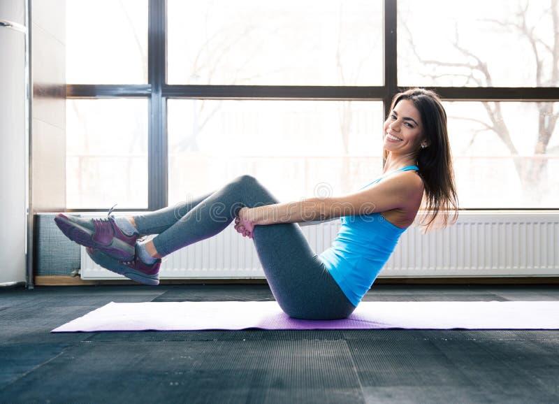 Mujer joven sonriente que hace ejercicio en la estera de la yoga fotos de archivo libres de regalías