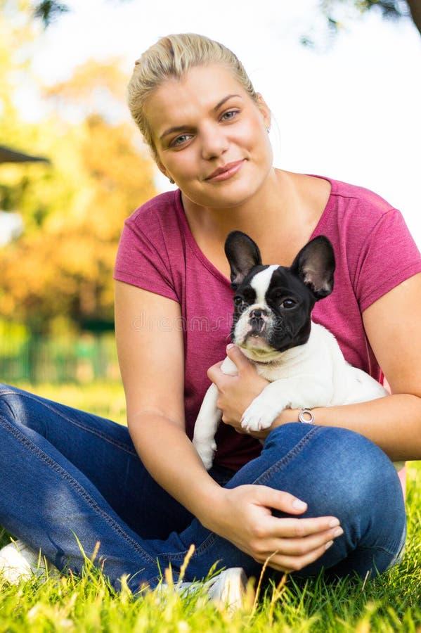 Mujer joven sonriente que juega con el perrito Su mejor amigo imagenes de archivo