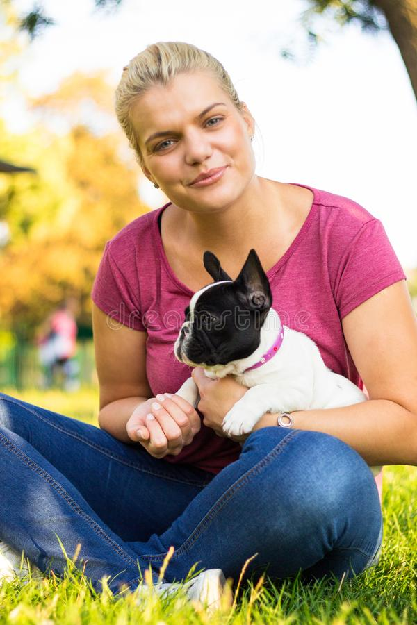 Mujer joven sonriente que juega con el perrito Su mejor amigo fotos de archivo