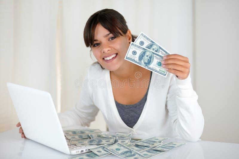 Mujer joven sonriente que le muestra el dinero del efectivo imágenes de archivo libres de regalías