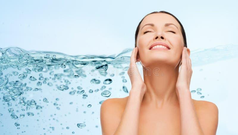 Mujer joven sonriente que limpia su cara sobre el agua foto de archivo libre de regalías