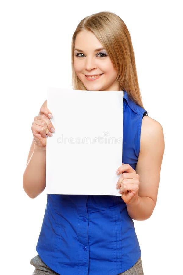 Mujer joven sonriente que lleva a cabo a la tarjeta blanca vacía fotos de archivo libres de regalías