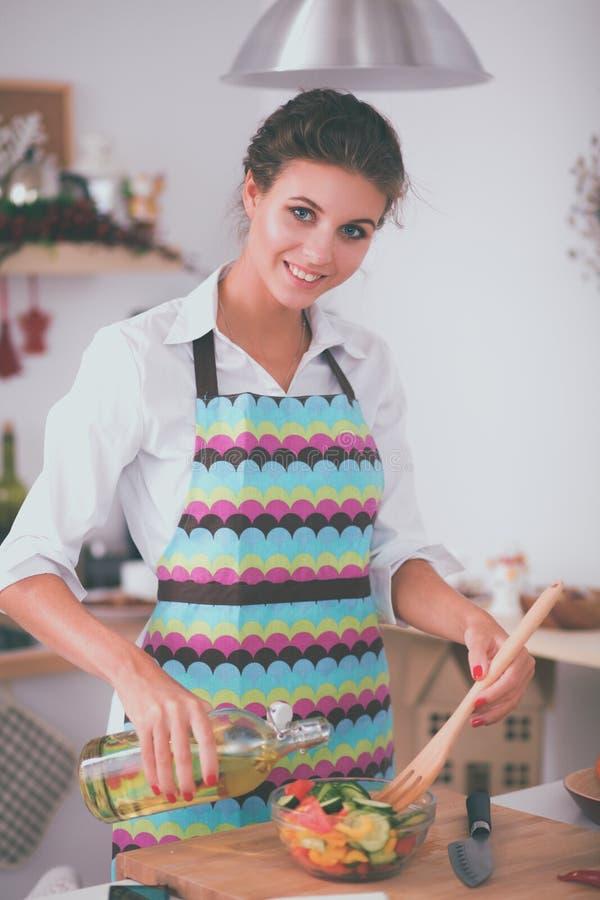 Mujer joven sonriente que mezcla la ensalada fresca en cocina foto de archivo