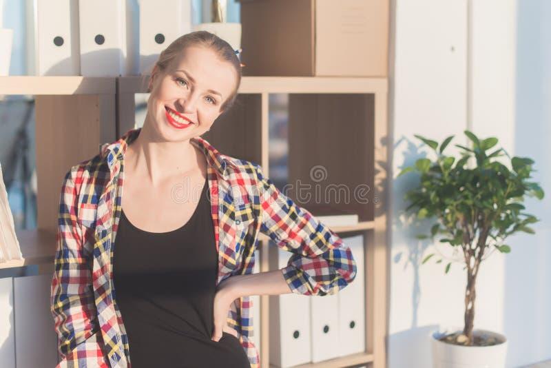 Mujer joven sonriente que mira la cámara, situación, cabeza que se inclina, poniendo la mano en el lado El trabajador de sexo fem fotos de archivo libres de regalías