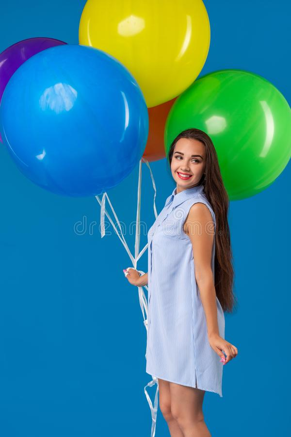 Mujer joven sonriente que mira la cámara y que sostiene los balones de aire coloridos aislados sobre azul imagen de archivo