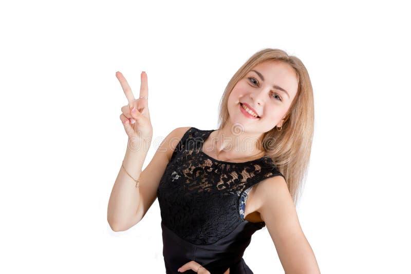 Mujer joven sonriente que muestra la muestra de la mano de la paz imagen de archivo