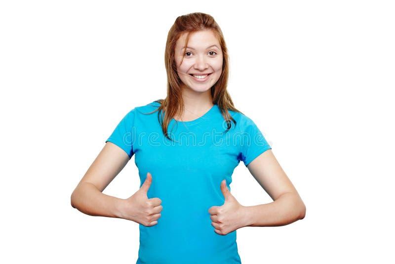 Mujer joven sonriente que muestra los pulgares para arriba fotografía de archivo