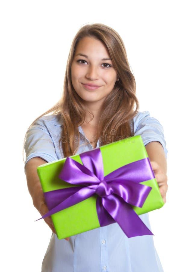 Mujer joven sonriente que muestra un regalo de la Navidad foto de archivo