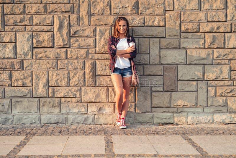 Mujer joven sonriente que se inclina contra una pared en la ciudad imagen de archivo