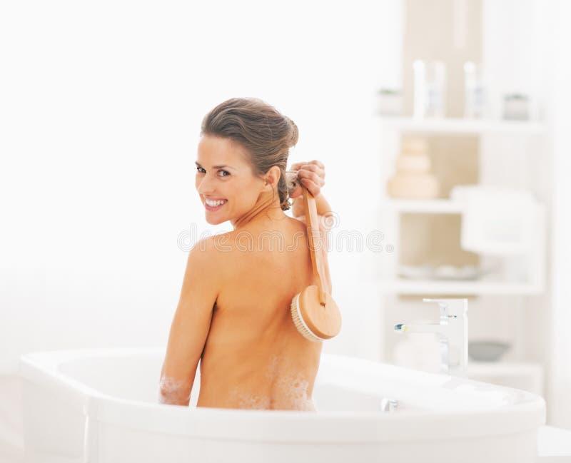 Mujer joven sonriente que se lava con el cepillo del cuerpo en bañera imagen de archivo libre de regalías