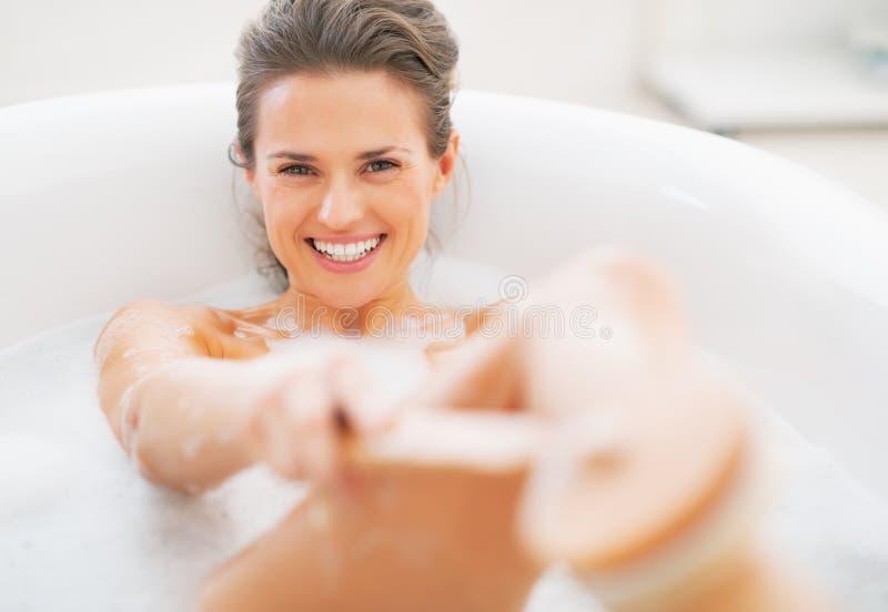 Mujer joven sonriente que se lava con el cepillo del cuerpo en bañera foto de archivo