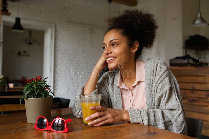 Mujer joven sonriente que se sienta en casa con el vidrio de zumo de naranja imagen de archivo libre de regalías