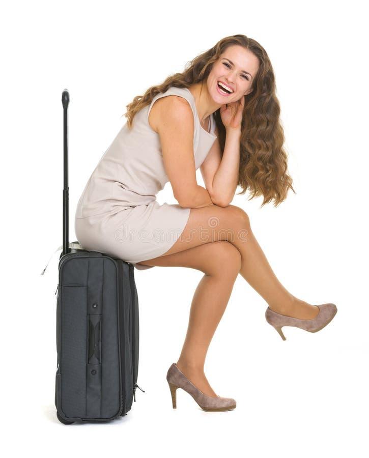 Mujer joven sonriente que se sienta en la maleta de las ruedas fotografía de archivo