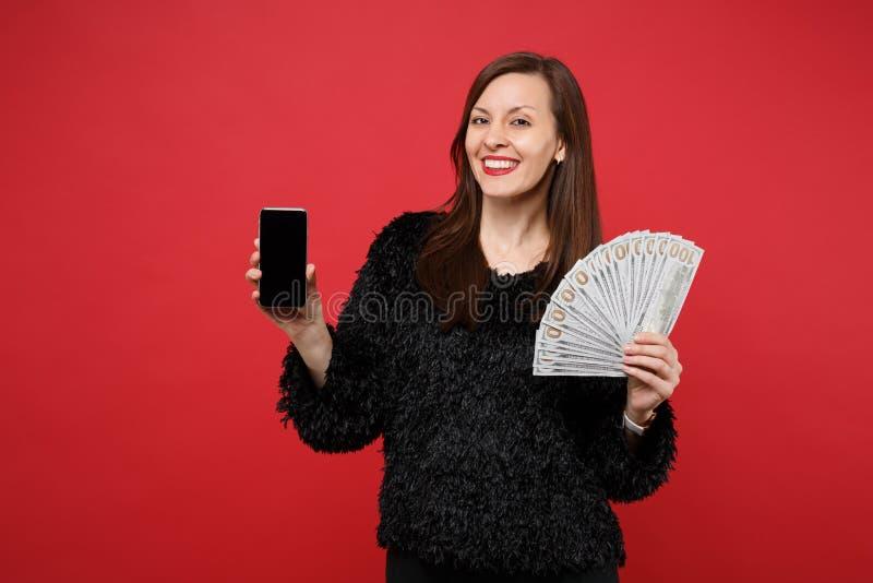 Mujer joven sonriente que sostiene el teléfono móvil con la fan vacía en blanco de la pantalla del dinero en el dinero del efecti fotografía de archivo