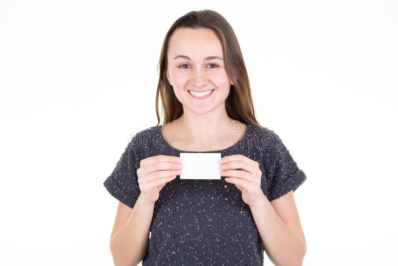 Mujer joven sonriente que sostiene la tarjeta vacía blanca del espacio en blanco en su mano con el espacio de la copia para el te fotos de archivo