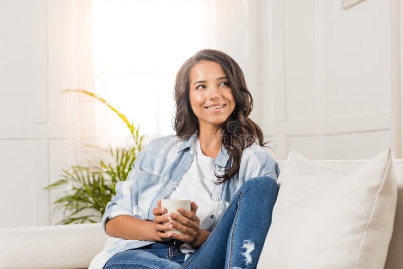 Mujer joven sonriente que sostiene la taza mientras que se sienta en el sofá y mira lejos en casa fotos de archivo libres de regalías