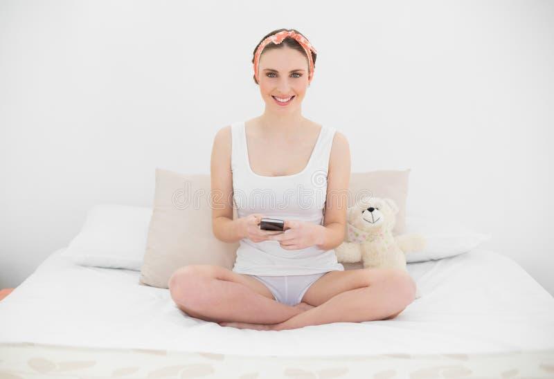 Mujer joven sonriente que sostiene su smartphone imagen de archivo