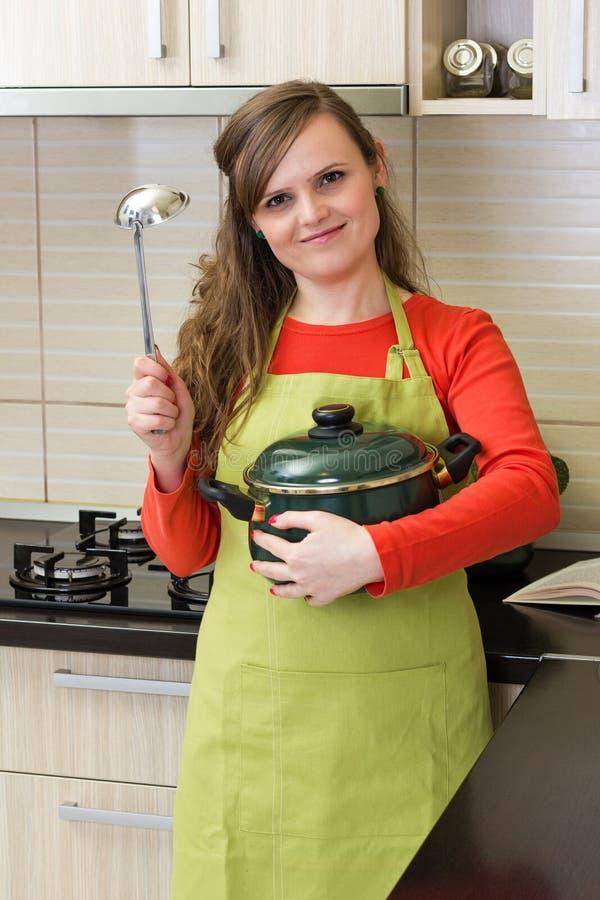 Mujer joven sonriente que sostiene un pote y una cucharón de sopa imagen de archivo libre de regalías