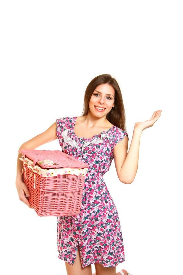 Mujer joven sonriente que sostiene una cesta de lavadero en el fondo blanco imagenes de archivo