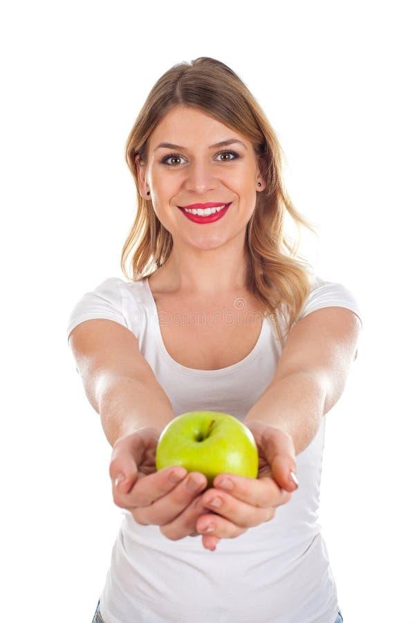 Mujer joven sonriente que sostiene una manzana verde fotos de archivo libres de regalías