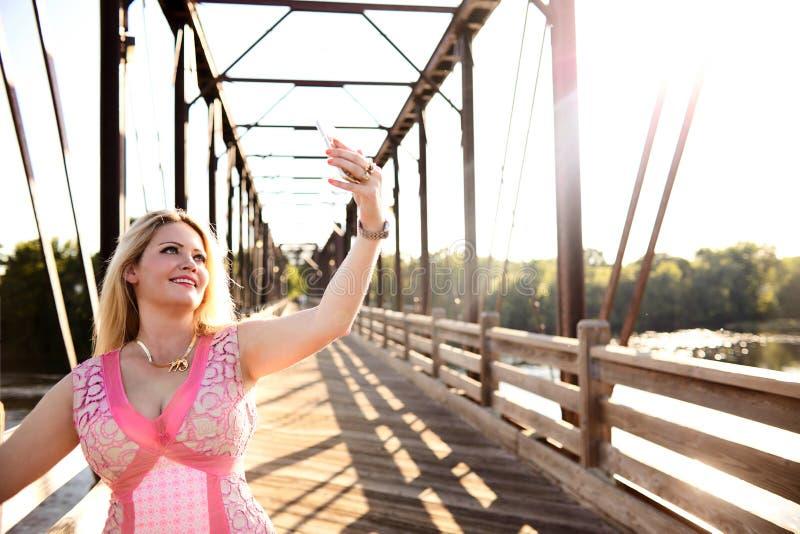 Mujer joven sonriente que toma el selfie en el puente foto de archivo