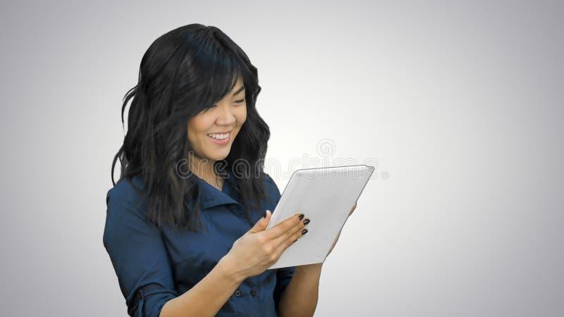 Mujer joven sonriente que trabaja en la tableta en el fondo blanco fotografía de archivo libre de regalías