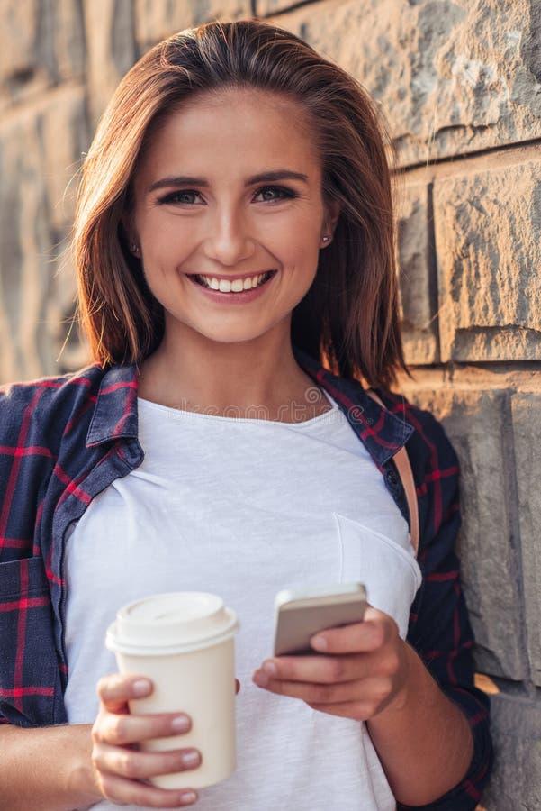 Mujer joven sonriente que usa un teléfono móvil en la ciudad fotos de archivo