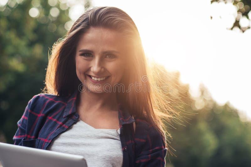 Mujer joven sonriente que usa una tableta digital afuera fotografía de archivo libre de regalías