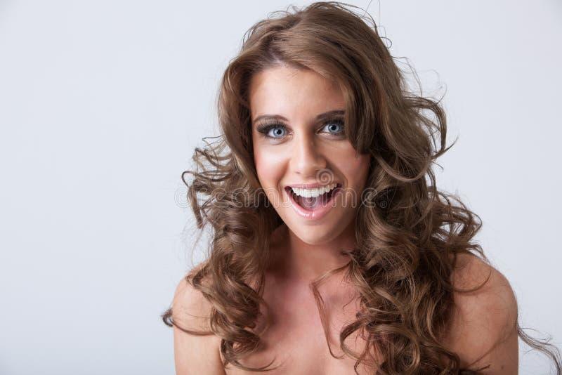Mujer joven sonriente Surprised con el pelo rizado largo sano foto de archivo