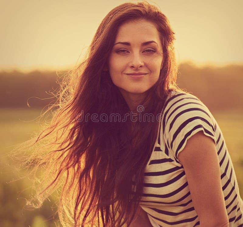 Mujer joven sonriente tranquila hermosa que parece feliz con el pelo brillante largo en fondo brillante del verano de la puesta d imagen de archivo