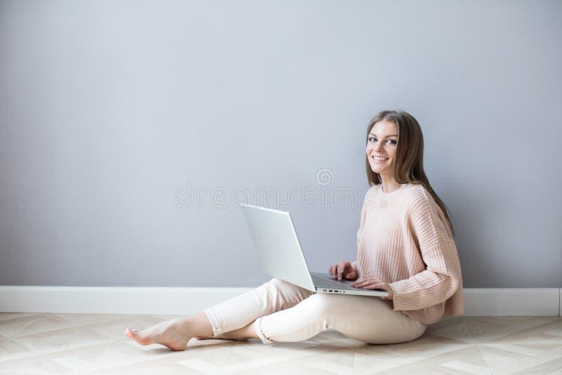 Mujer joven sonriente usando un ordenador portátil que se sienta en un piso de madera imagen de archivo libre de regalías