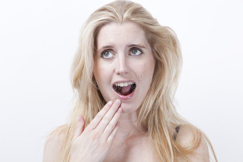Mujer joven sorprendida con la boca abierta contra el fondo blanco fotos de archivo libres de regalías