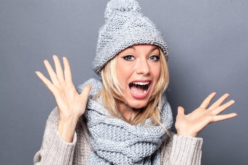 Mujer joven sorprendida con la bufanda y el sombrero del invierno que se divierten fotos de archivo