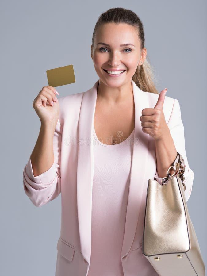 Mujer joven sorprendida emocionada alegre con la tarjeta de crédito aislada imagenes de archivo
