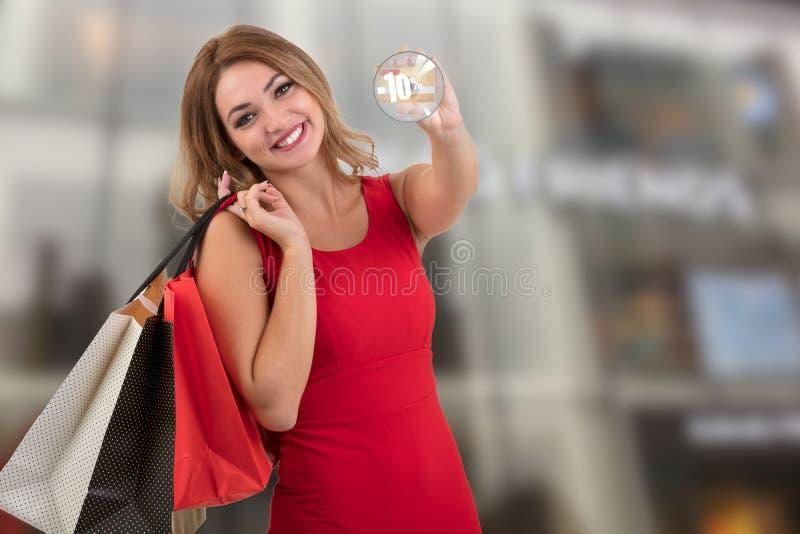 Mujer joven sorprendida emocionada alegre con la tarjeta de crédito con el ejemplo de la venta fotografía de archivo libre de regalías