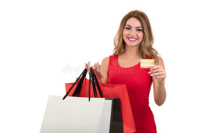 Mujer joven sorprendida emocionada alegre con la tarjeta de crédito sobre el fondo blanco fotos de archivo